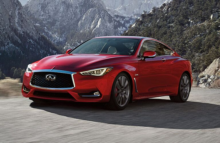 Red 2017 INFINITI Q60 driving on a mountainous road