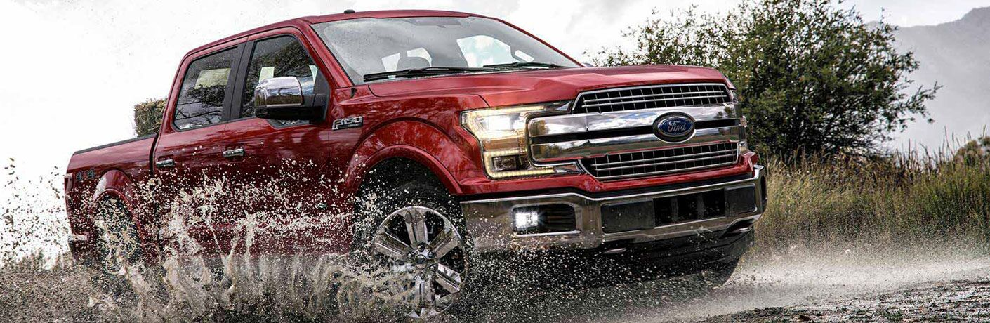 Red 2018 Ford F-150 driving on a wet and muddy road
