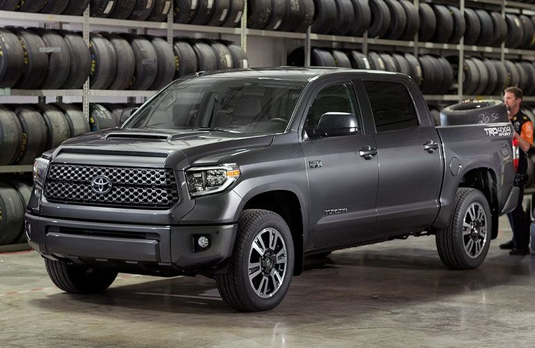 Grey 2018 Toyota Tundra parked next to a wall of tires