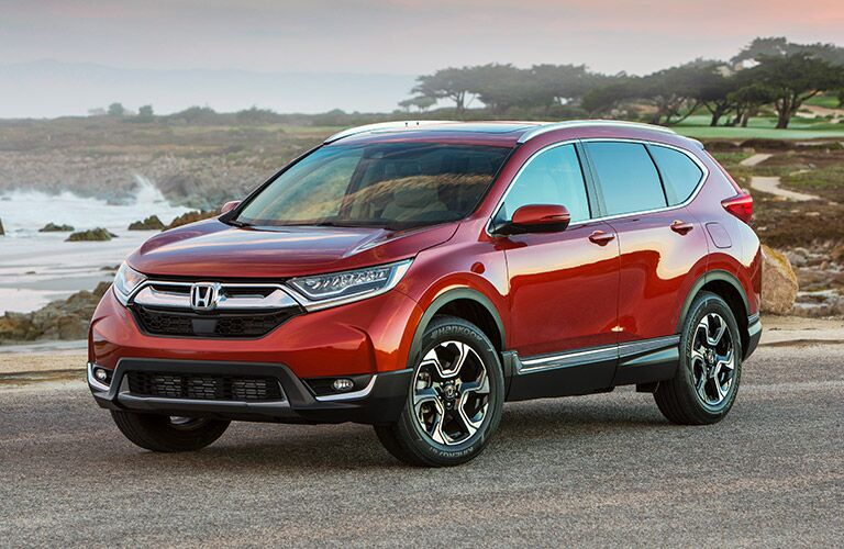 2019 Honda CR-V exterior shot with red paint color parked on a gravel beach near seaside trees and ocean waves