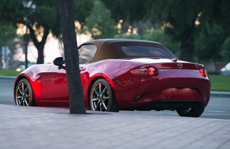 Red 2019 Mazda MX-5 Miata Soft Top parked by a sidewalk