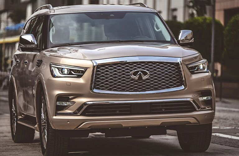 2020 Infiniti QX80 exterior front shot with beige paint color driving through an urban city setting