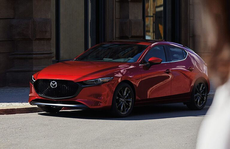 2020 Mazda3 Hatchback exterior shot with red paint color parked on the side of a street as a woman approaches