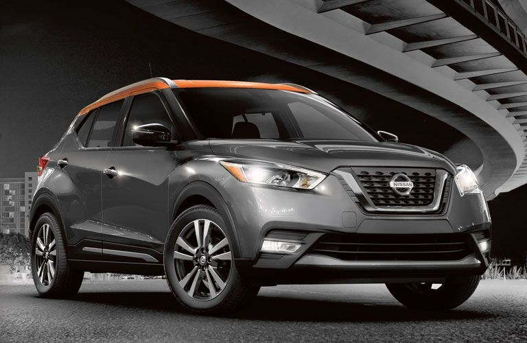 2020 Nissan Kicks exterior shot with gray body and orange roof parked under a steel bridge in the city