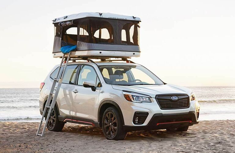 2020 Subaru Forester exterior shot with white paint color parked on a beach with a camper and ladder installed on its roof rails
