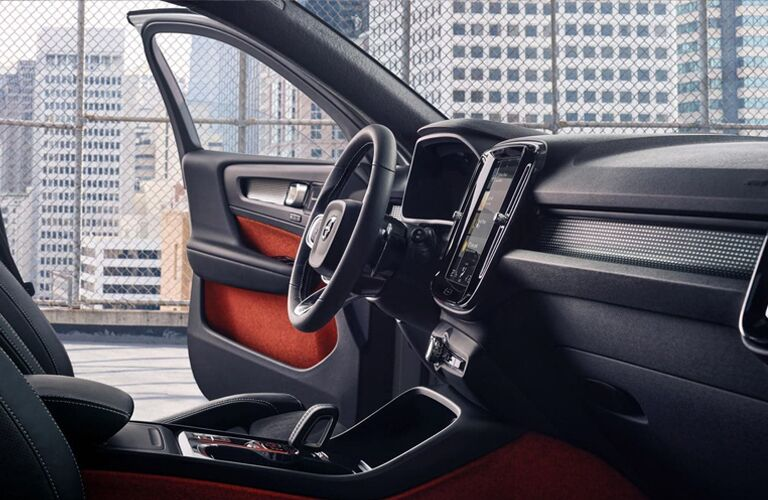2020 Volvo XC40 interior side shot of front seating, transmission, and steering wheel with an urban skyscraper background outside