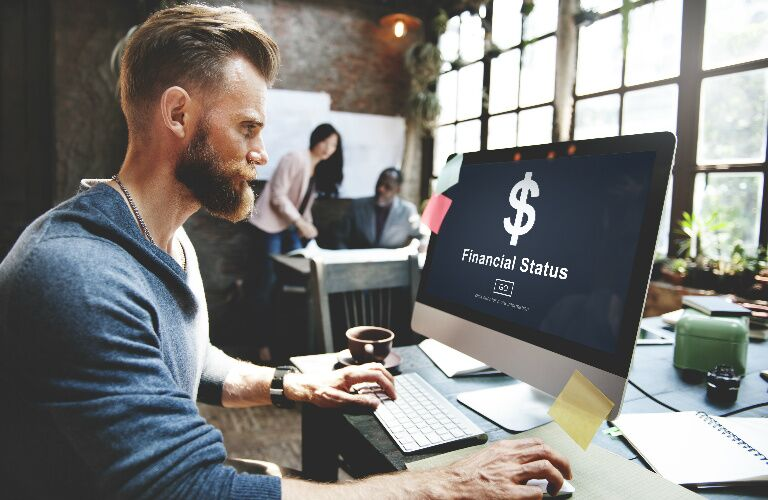 Hipster Guy Looking at Financial Information on a Computer