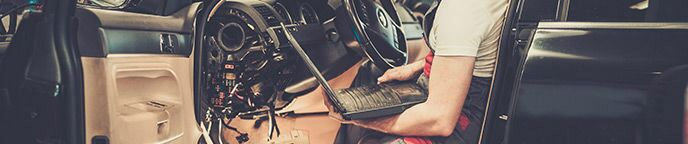 Technician Holding a Laptop Computer Inside a Car