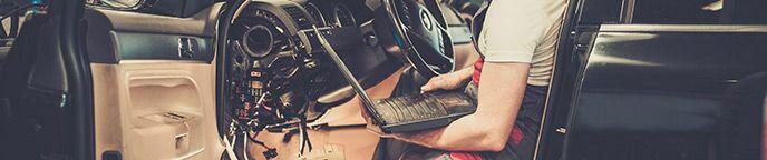 Technician Holding a Laptop Computer Inside a Car