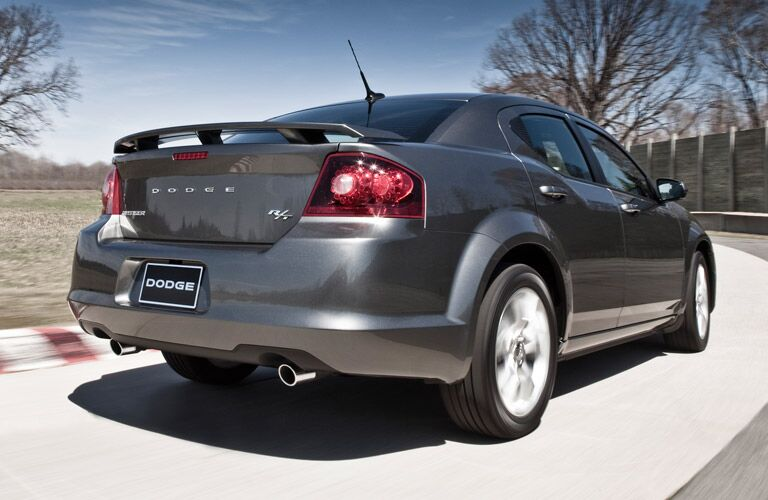 2013 Dodge Avenger drives around a track. Exterior rear angled view.