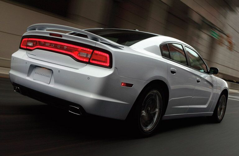 2013 Dodge Charger cruises along a city street so fast that the surroundings are blurred.