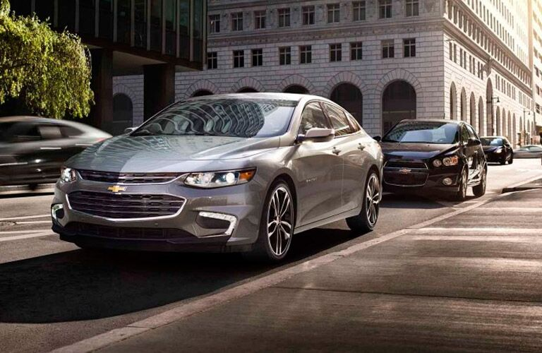 Silver 2017 Chevy Malibu drives down a city street in broad daylight. Exterior angled front/side view. A second Chevy Malibu follows closely behind.