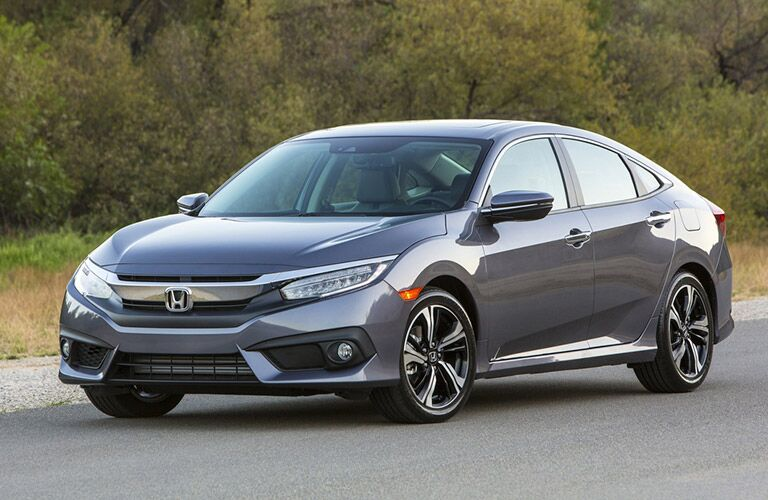 Grey 2017 Honda Civic sedan drives down a highway. Exterior angled front/side view.