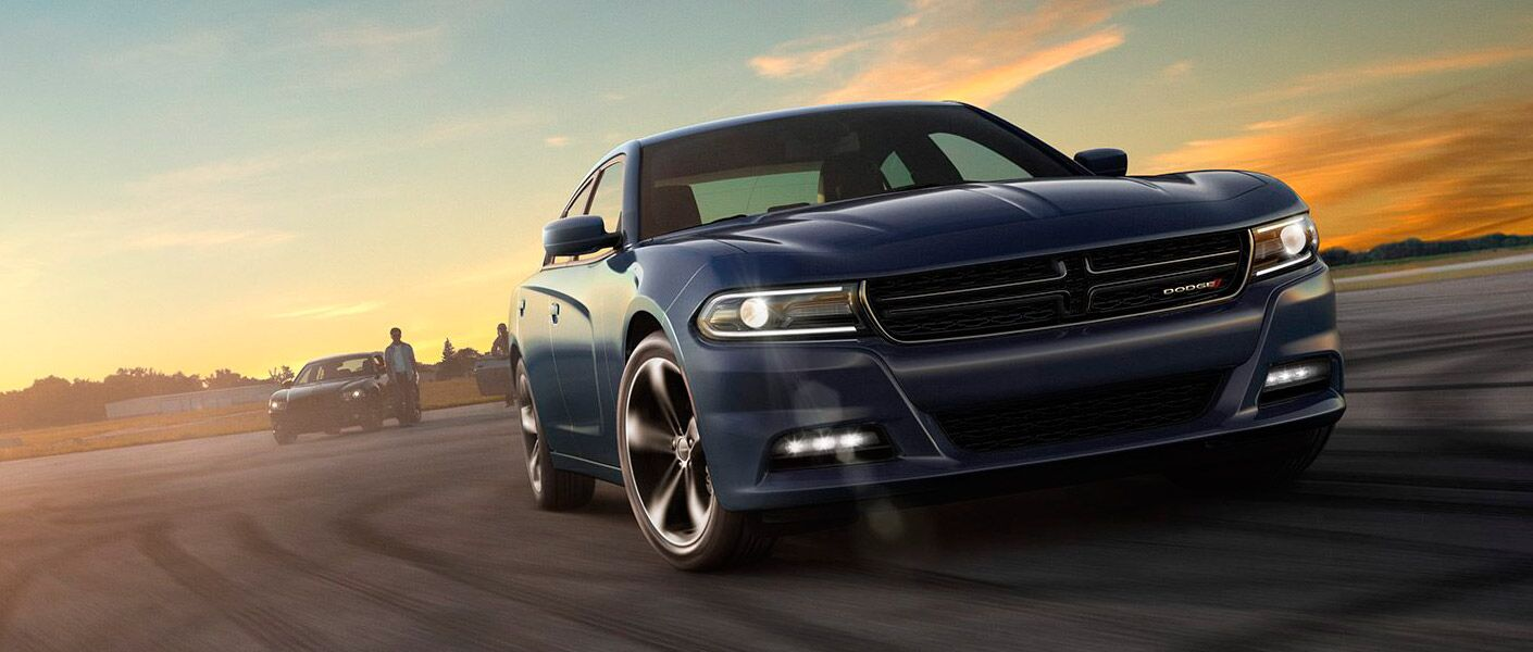 2017 Dodge Charger exterior front view on a track at sunrise.