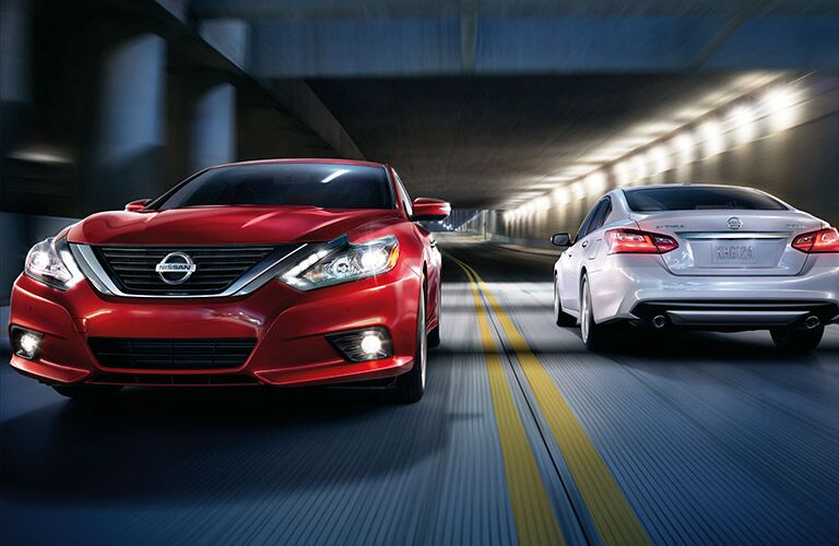 Red 2017 Nissan Altima drives out from a tunnel on a highway, passing a white 2017 Nissan Altima going the opposite direction.