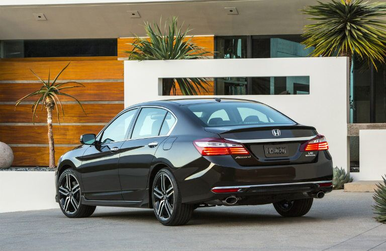 Black 2017 Honda Accord sedan parked in front of a house with palm trees.
