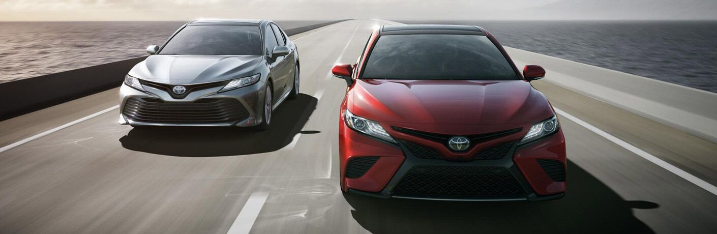 Two 2018 Toyota Camry vehicles drive down a highway bridge over a body of water. Head-on view of red and white colored models.