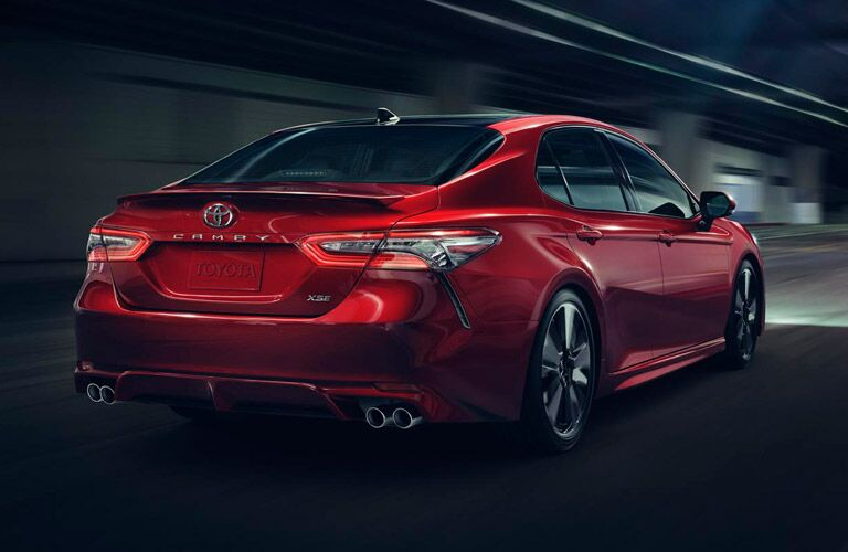 """Red 2018 Toyota Camry drives down a dark city street. Rear angled view highlighting the """"Toyota"""" emblem and """"Camry"""" name tag."""