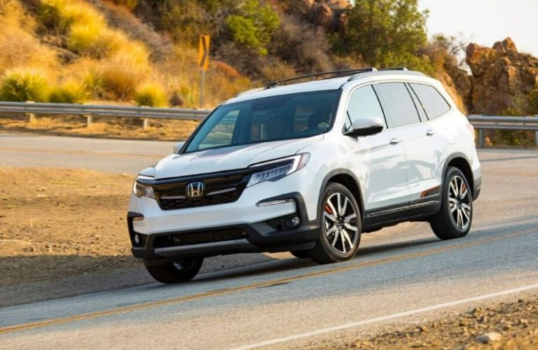 2020 Honda Pilot driving down road from exterior front drivers side