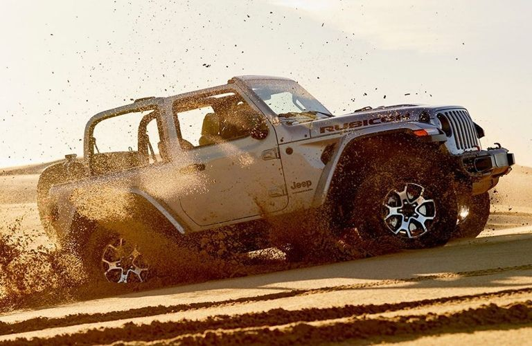 2020 Jeep Wrangler driving through sand from exterior passenger side