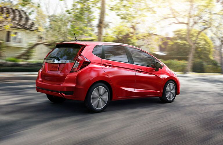 Red 2017 Honda fit cruises along a suburban street. Exterior side/rear view.