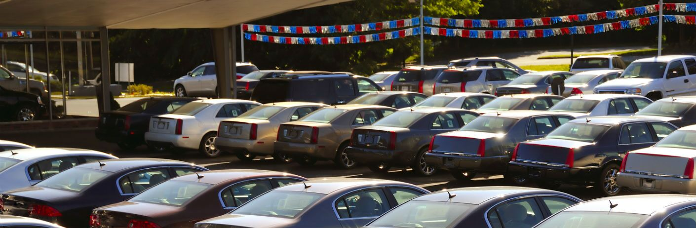 Many cars on a sunny lot underneath red, white, and blue streamers.