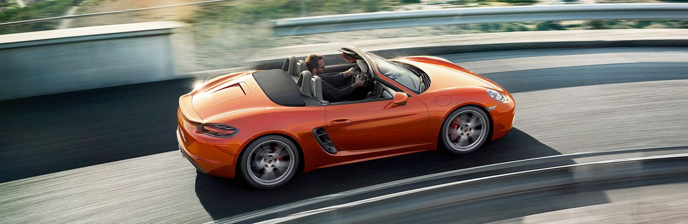 person driving an orange 718 Boxster