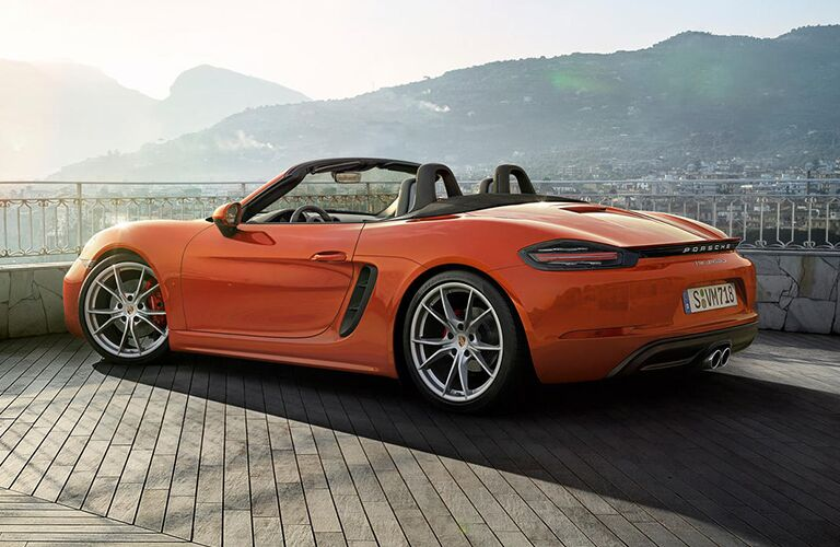 2019 Porsche 718 Boxster exterior side shot with orange paint color parked on a wooden balcony overlooking a city under a sunset