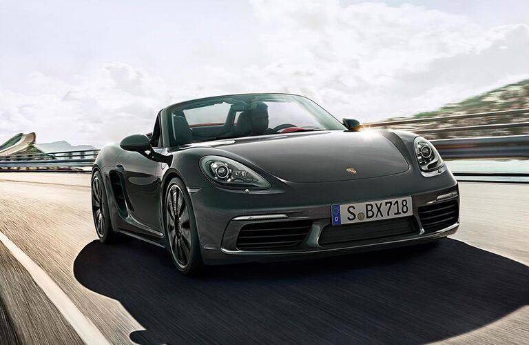 2019 Porsche 718 Boxster exterior front shot with gray paint color driving down a highway