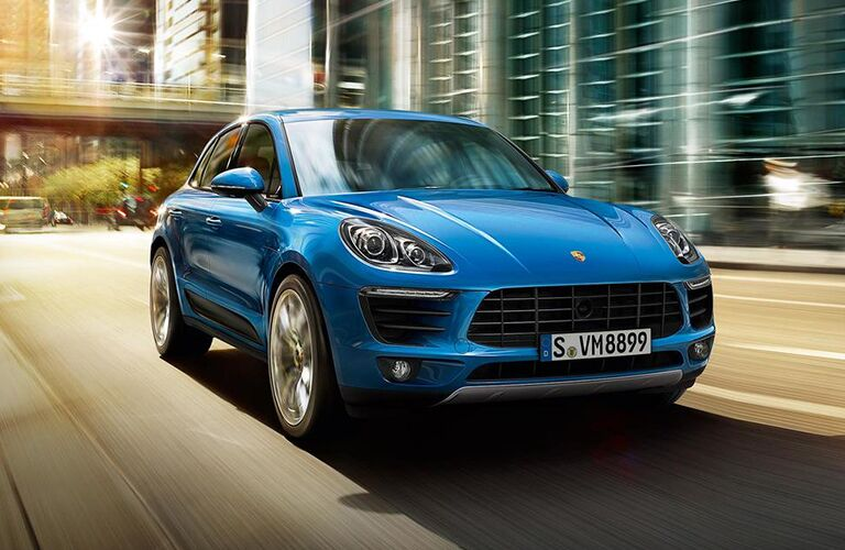 2019 Porsche Macan exterior front fascia and passenger side going fast on blurred city road