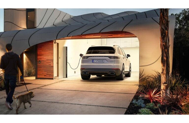 2019 Porsche Cayenne E-Hybrid exterior rear shot parked inside a luxury home's garage while plugged in and charging