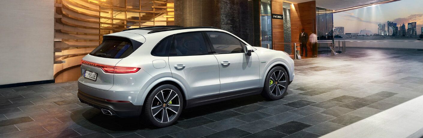 2019 Porsche Cayenne E-Hybrid exterior rear side shot with gray white paint color parked outside a fancy hotel restaurant lobby elevator