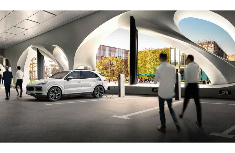 2019 Porsche Cayenne E-Hybrid exterior shot with white paint color plugged into a public charging station as office workers pass by
