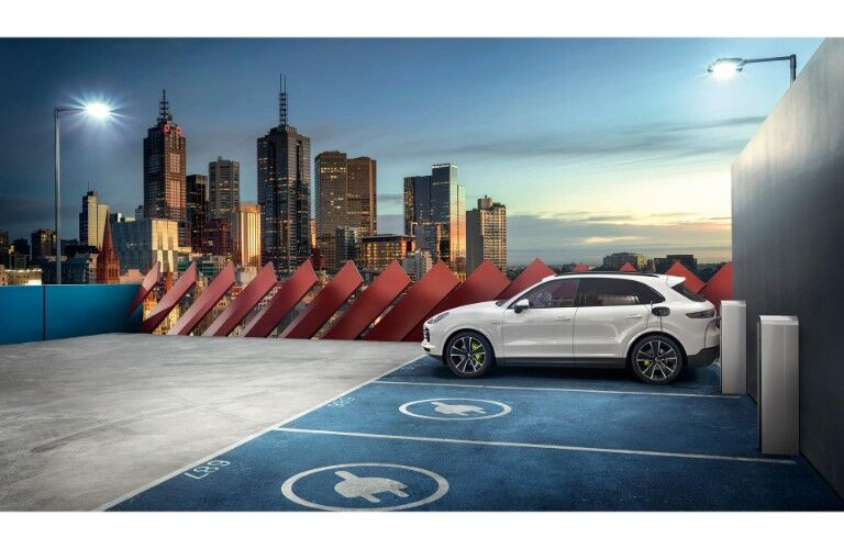 2019 Porsche Cayenne E-Hybrid exterior side shot with white paint color parked on a rooftop at a charging station with a city skyline of skyscrapers in the background