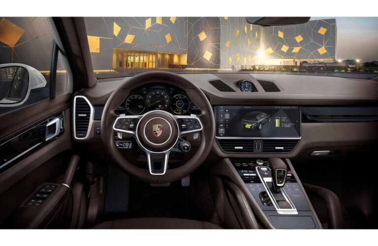 2019 Porsche Cayenne E-Hybrid interior driver's seat view shot of steering wheel with Porsche badge, infotainment dashboard display, and transmission with trimming