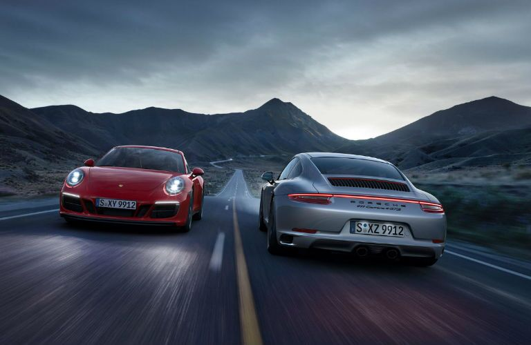 2019 Porsche 911 Carrera GTS and 2019 Porsche 911 Carrera GTS Cabriolet driving opposite ways on desert road at night
