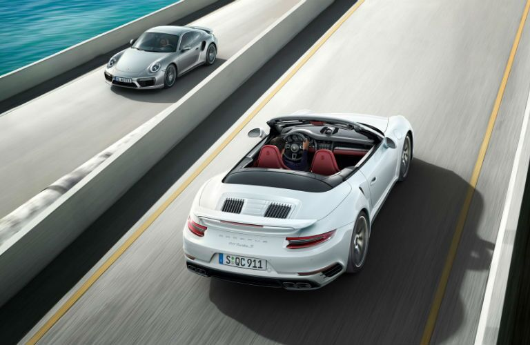 2019 Porsche 911 Turbo cabriolet driving one way and a 911 Turbo going the other way on a highway