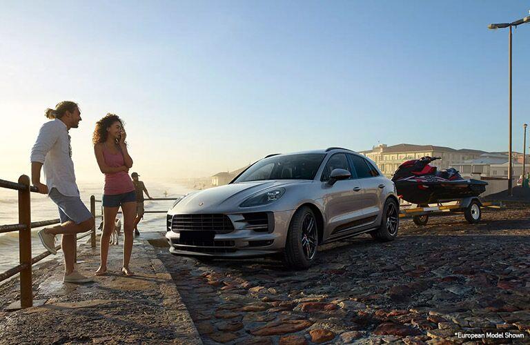 A couple on the beach with their 2020 Porsche Macan