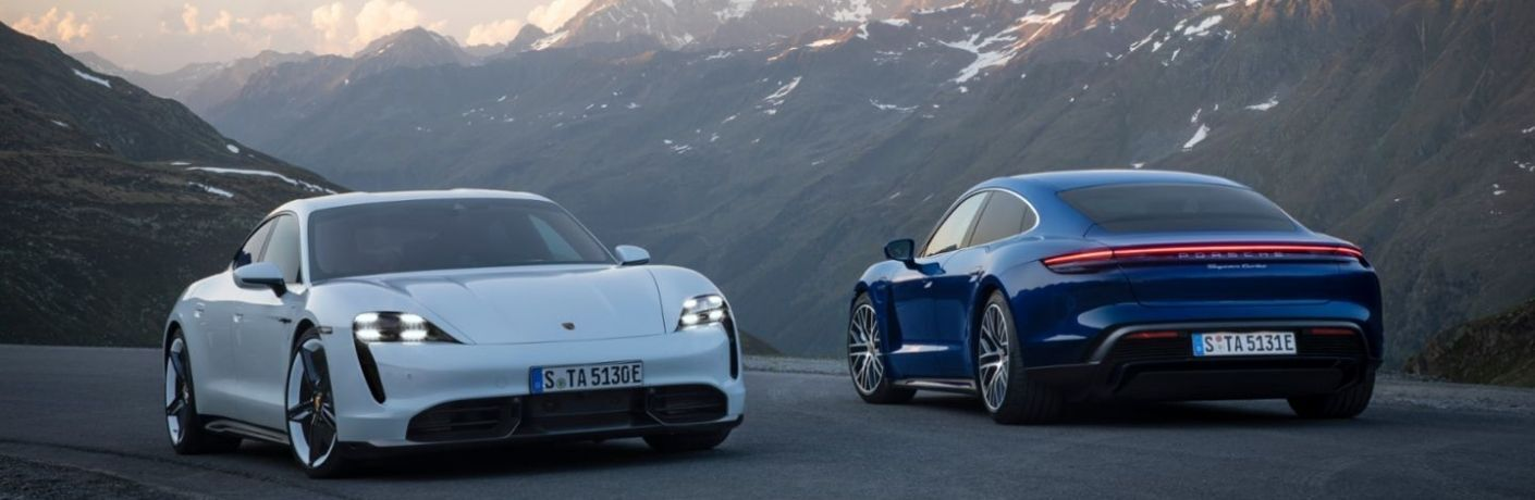 Two 2021 Porsche Taycan passing by each other on road