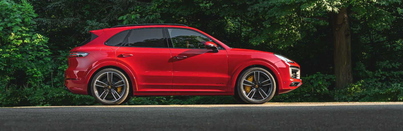 A right profile photo of the 2021 Porsche Cayenne GTS parked in the woods.