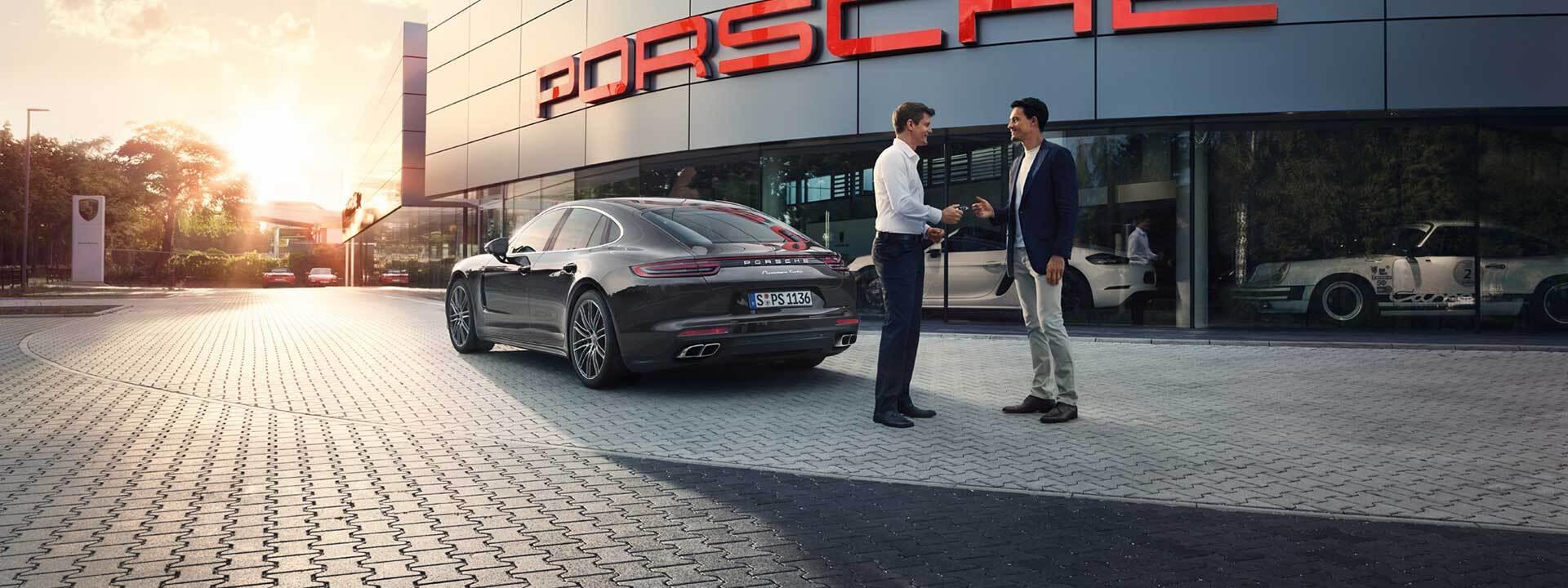 Two people exchanging keys to a Porsche in Newark, DE