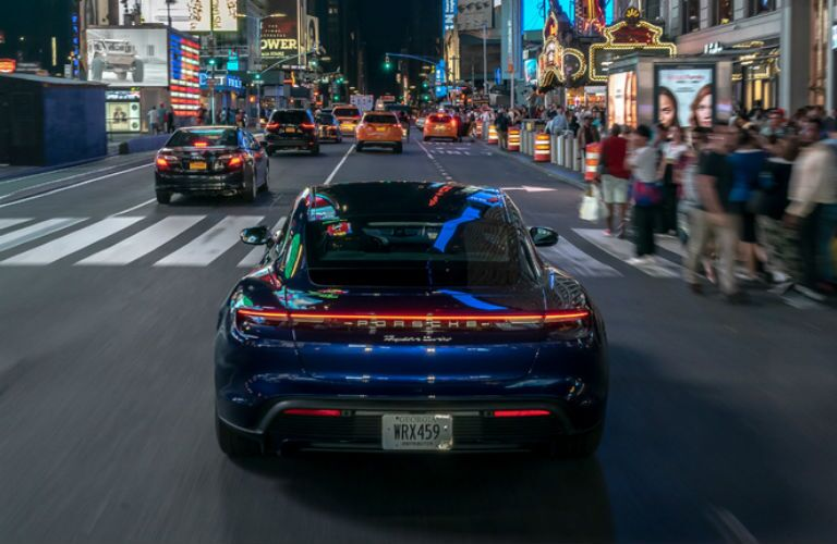 rear view of blue 2020 Porsche Taycan Turbo driving in city