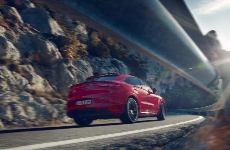 2020 Porsche Cayenne red driving on rocky road shot under guardrail