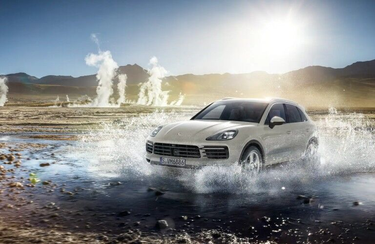2020 Porsche Cayenne white driving through puddle with geysers in background