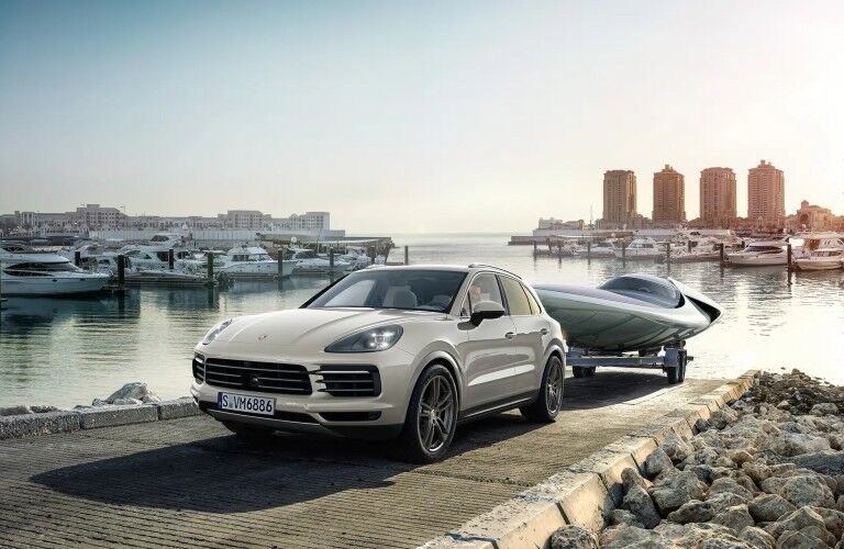 2020 Porsche Cayenne white towing boat to waterfront