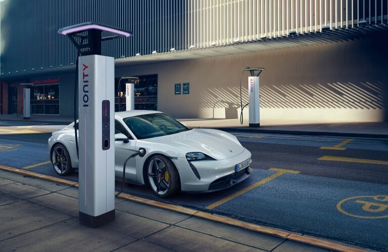 White 2020 Porsche Taycan Charging on a City Street