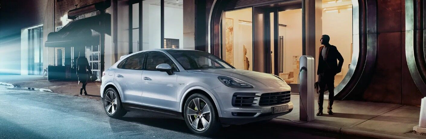 2021 Porsche Cayenne silver charging on side of street at night