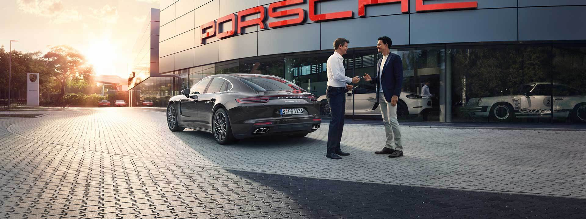 Two people exchanging keys to a Porsche in Colorado Springs, CO