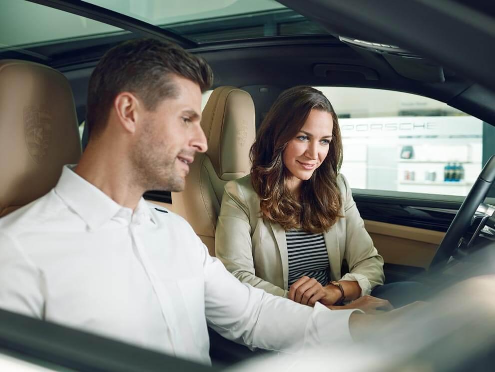 A couple sitting in a Porsche in Colorado Springs, CO