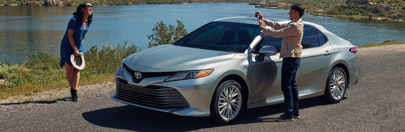 man taking picture of woman by 2019 camry hybrid